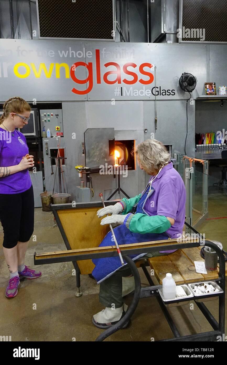 Visitatore femmina indossando indumenti protettivi laminazione di un cannello con attaccato il vetro fuso, guardato da un museo glassblower. Corning Museo del Vetro Immagini Stock