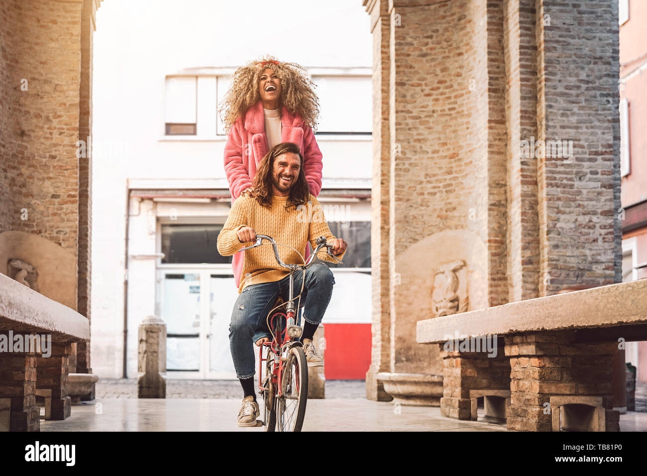 Coppia felice di andare in bicicletta nel centro città - Giovani avendo divertimento outdoor - generazione millenaria e gioventù il concetto di stile di vita Foto Stock