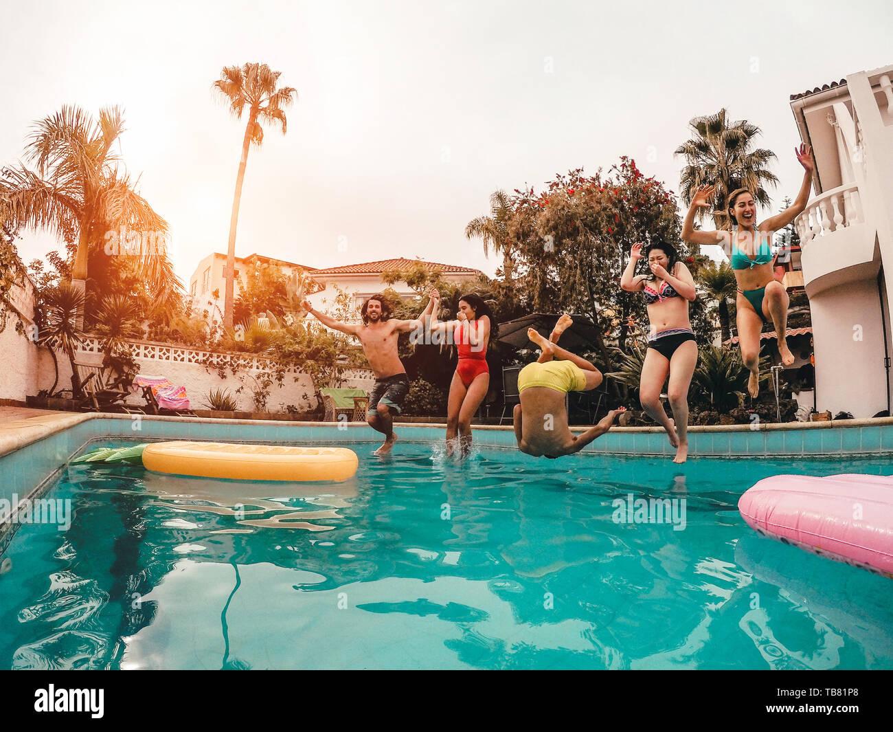 Gruppo di amici felice del salto in piscina al tramonto - Crazy giovani divertirsi facendo parte in esclusiva casa tropicale Foto Stock