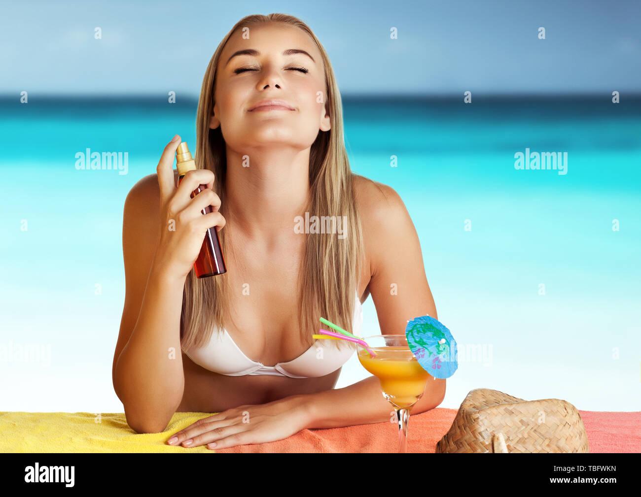 Ritratto di una bella donna sulla spiaggia utilizzando spf spray, l'applicazione di crema solare per proteggere la sua pelle dalle scottature, felice e sano soggiorno sulla spiaggia Immagini Stock