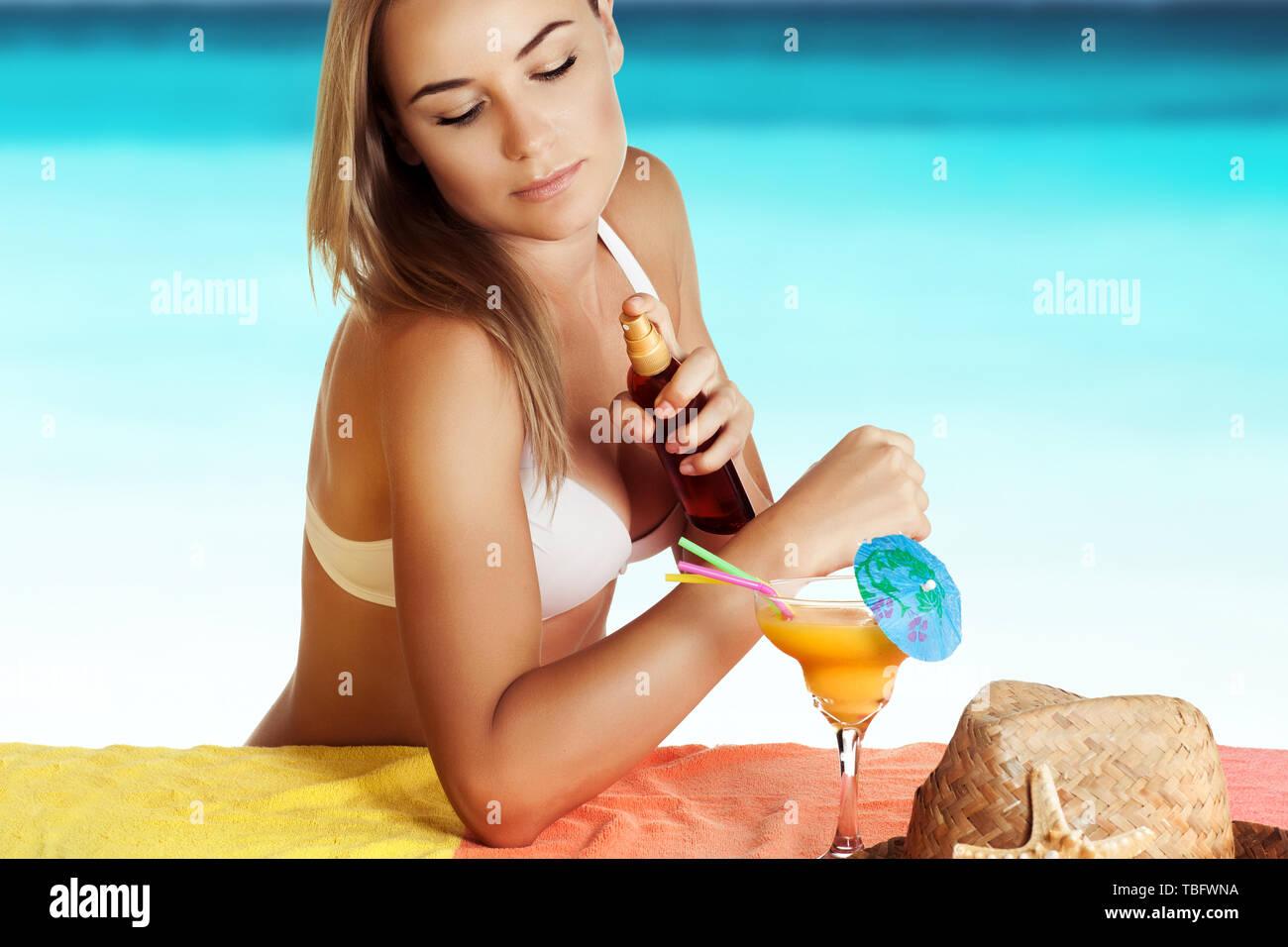 Bella ragazza a prendere il sole sulla spiaggia, utilizza una protezione solare spray per una abbronzatura sicura e divertente vacanza estiva vicino al mare, cura della pelle concept Immagini Stock