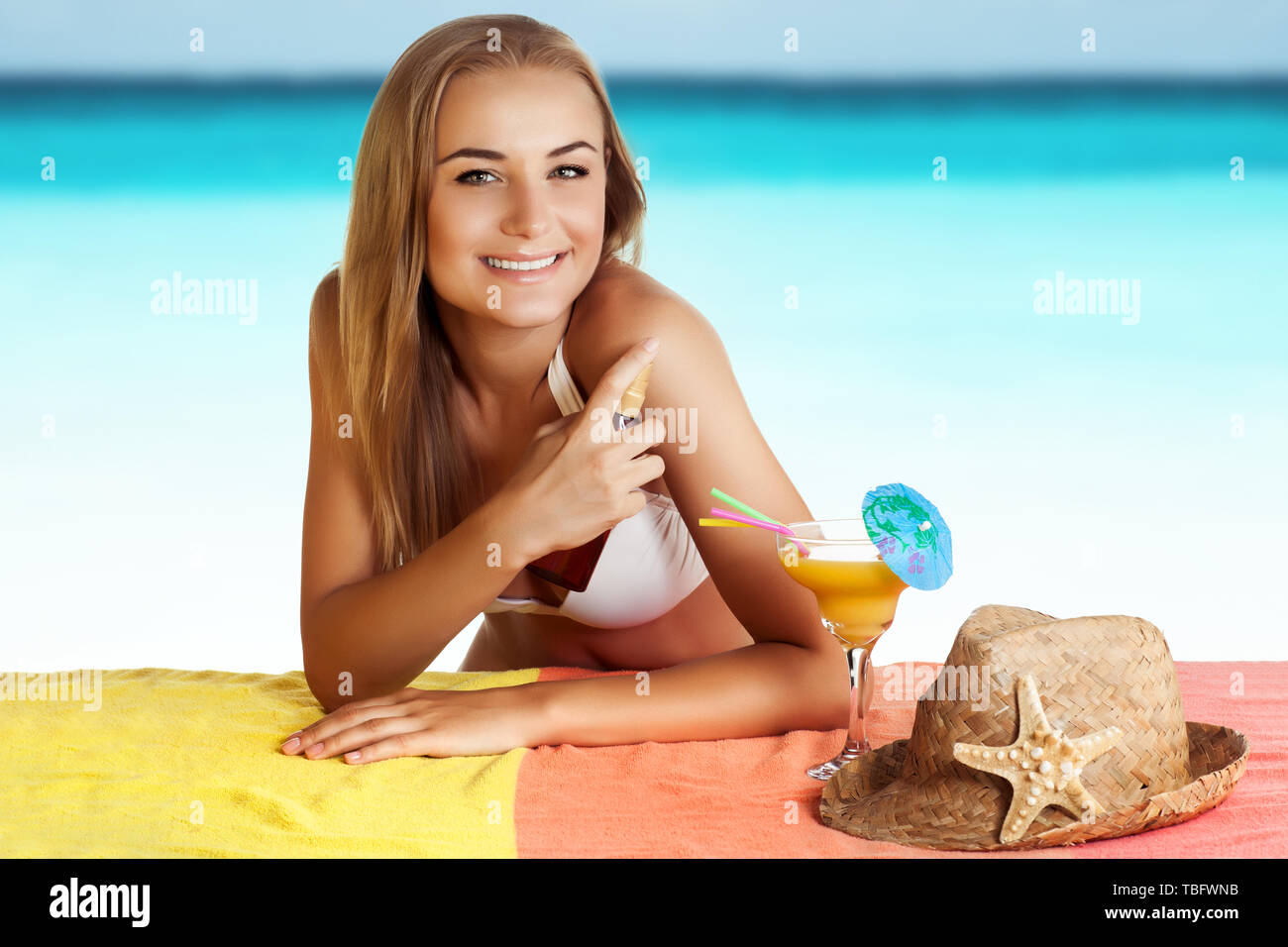 Ritratto di una bella donna sorridente con il piacere di trascorrere del tempo sulla spiaggia, utilizza una protezione solare spray per un sicuro tan, applicando anti-invecchiamento idratante Immagini Stock