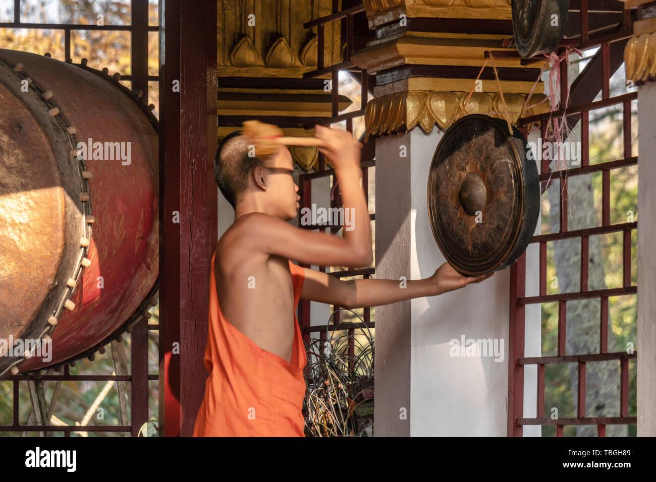 Wat Xieng Thong tempio, Sito Patrimonio Mondiale dell'UNESCO, il giovane monaco bhuddist drumming , debuttante alla cerimonia serale, Luang Prabang Immagini Stock