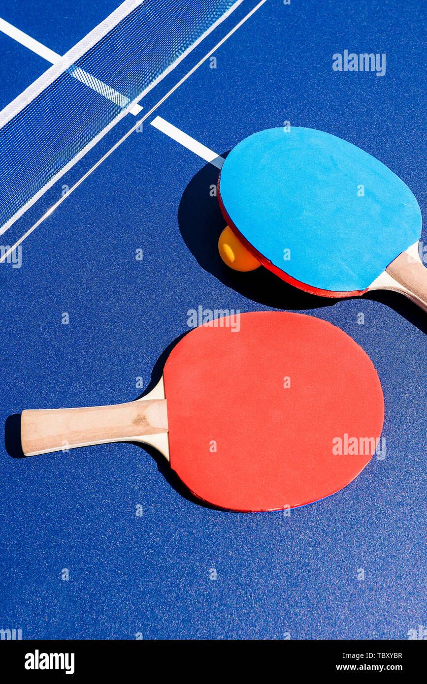 Racchette sul tavolo da ping pong e sfera arancione. Ping pong e tavolo da ping pong. Sport e attività all'aperto. Uno stile di vita sano. Banner in un impianto sportivo Immagini Stock