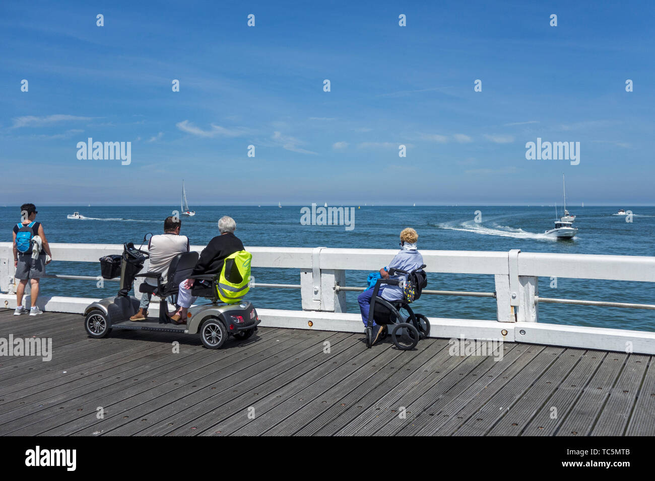 Donna disabile in carrozzina e per persone handicappate in duo due persona scooter di mobilità a guardare le barche in mare dal jetty Immagini Stock