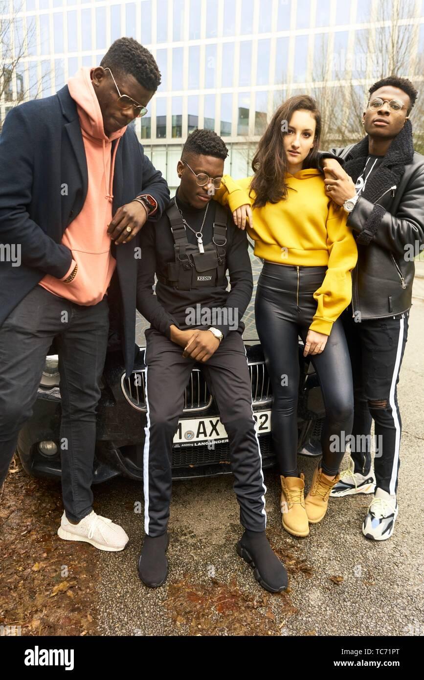 Raffreddare gli amici di moda pista appoggiata contro auto in città, cultura giovanile a Monaco di Baviera, Germania Immagini Stock