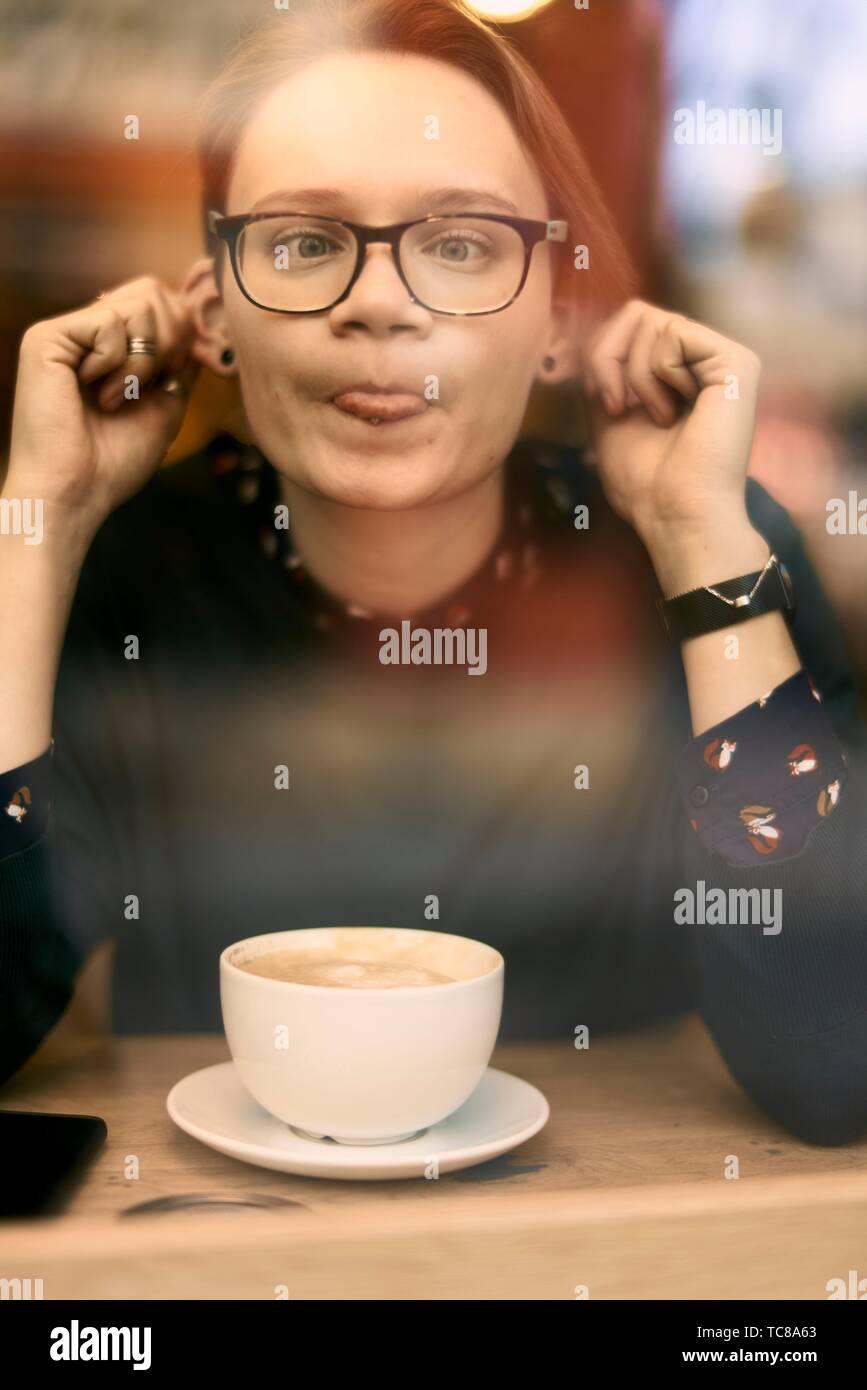 Ribelle donna dietro il vetro della finestra in café tirando dalle sue orecchie e linguetta sporgente, Monaco di Baviera, Germania. Foto Stock