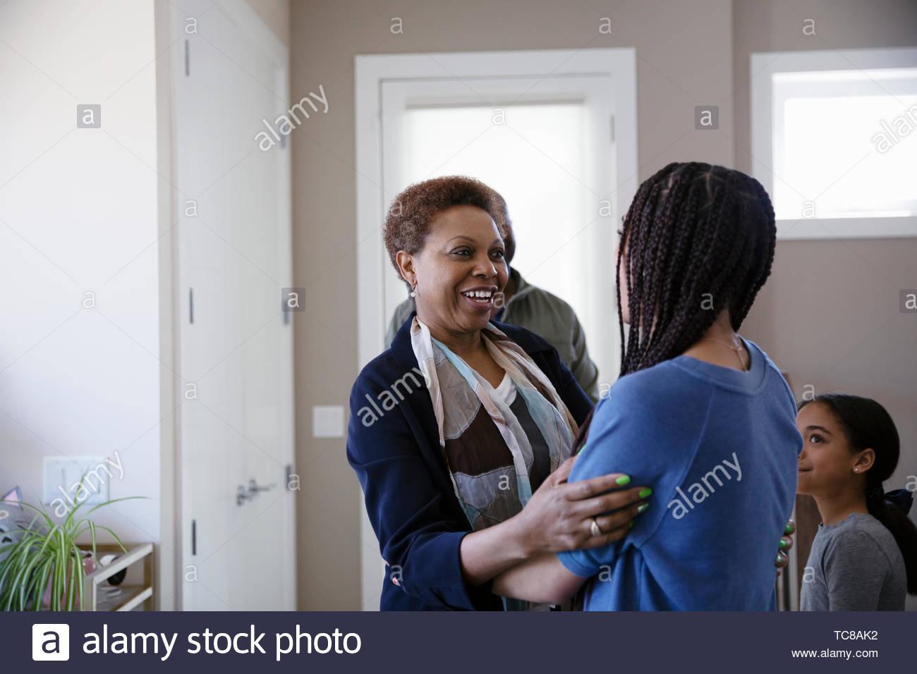 La nipote saluto, abbracciando la nonna Immagini Stock