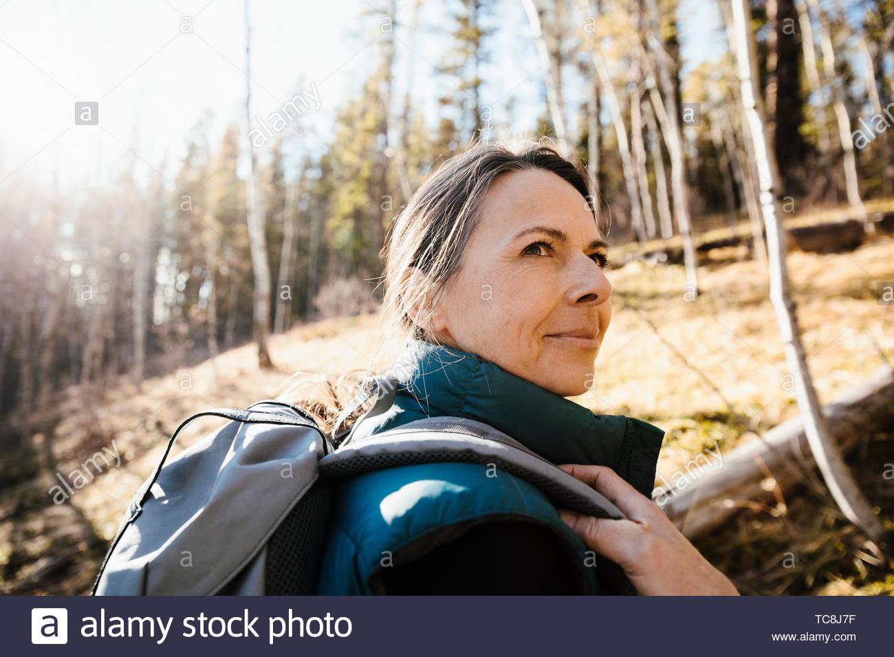Donna matura escursionismo nella soleggiata boschi Immagini Stock