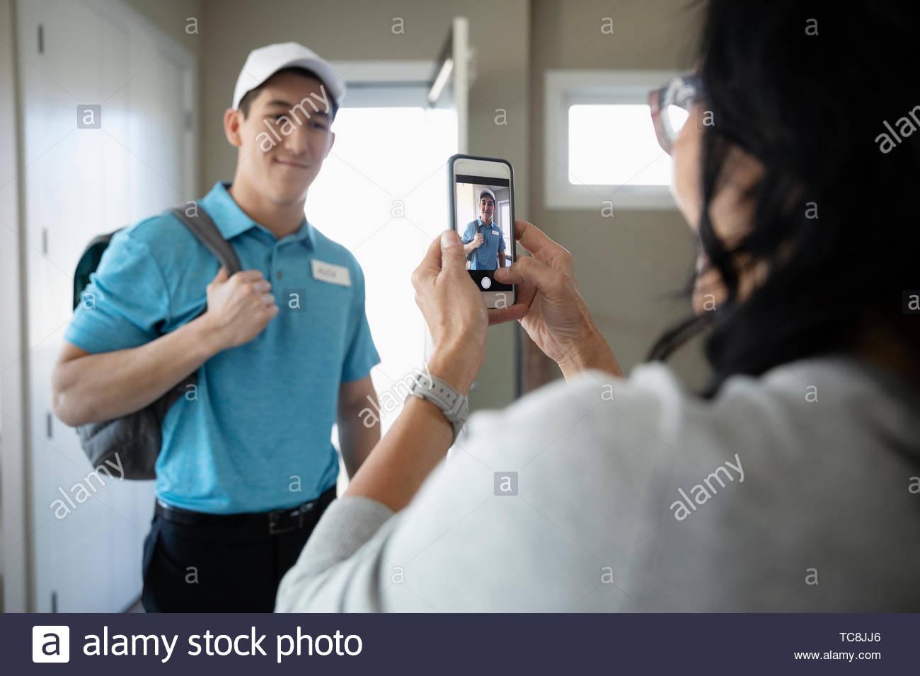 Mamma orgogliosa con la fotocamera del telefono a fotografare il nostro figlio adolescente in uniforme di lavoro Immagini Stock