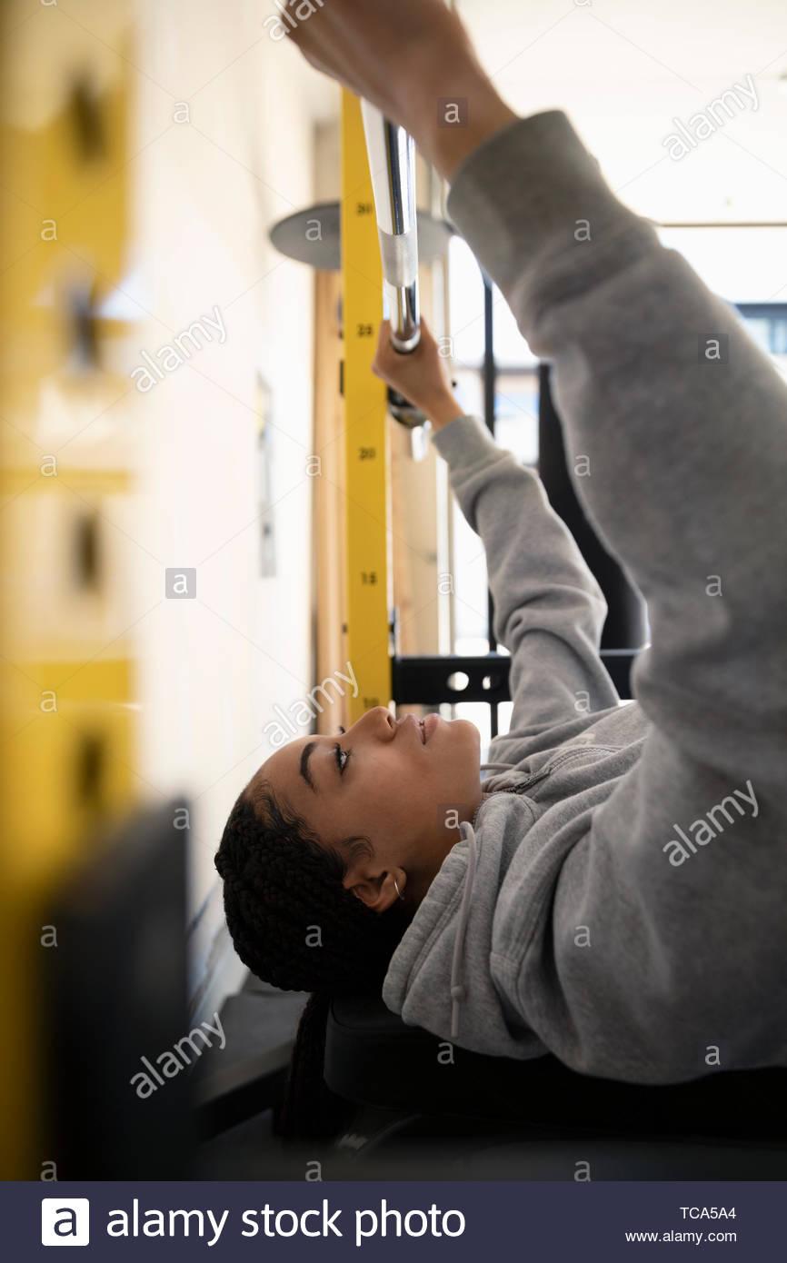 Focalizzato ragazza adolescente che lavora fuori, sollevamento pesi Immagini Stock