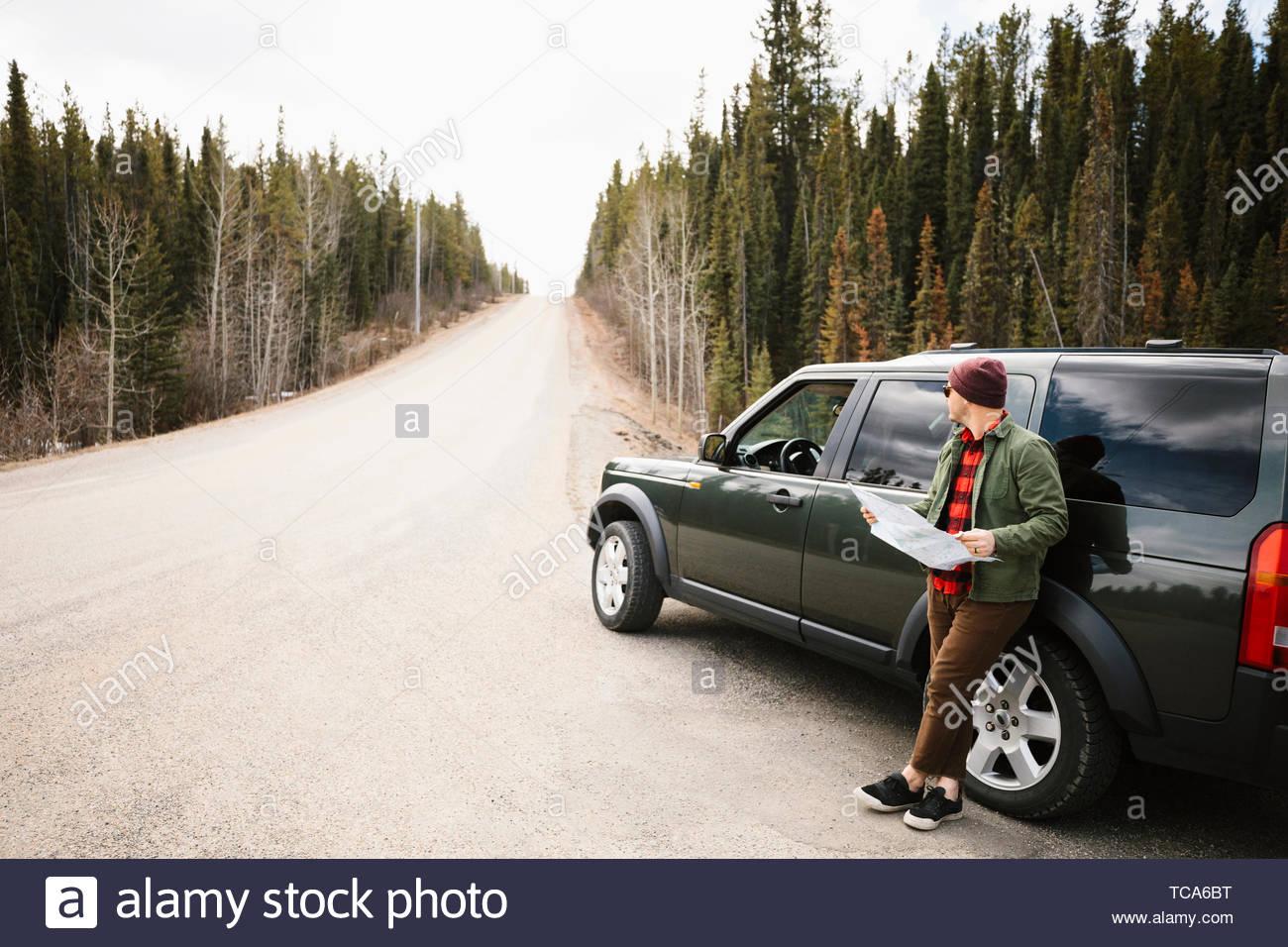 L'uomo con la mappa in piedi al di fuori di un SUV in remoto in banchina Immagini Stock