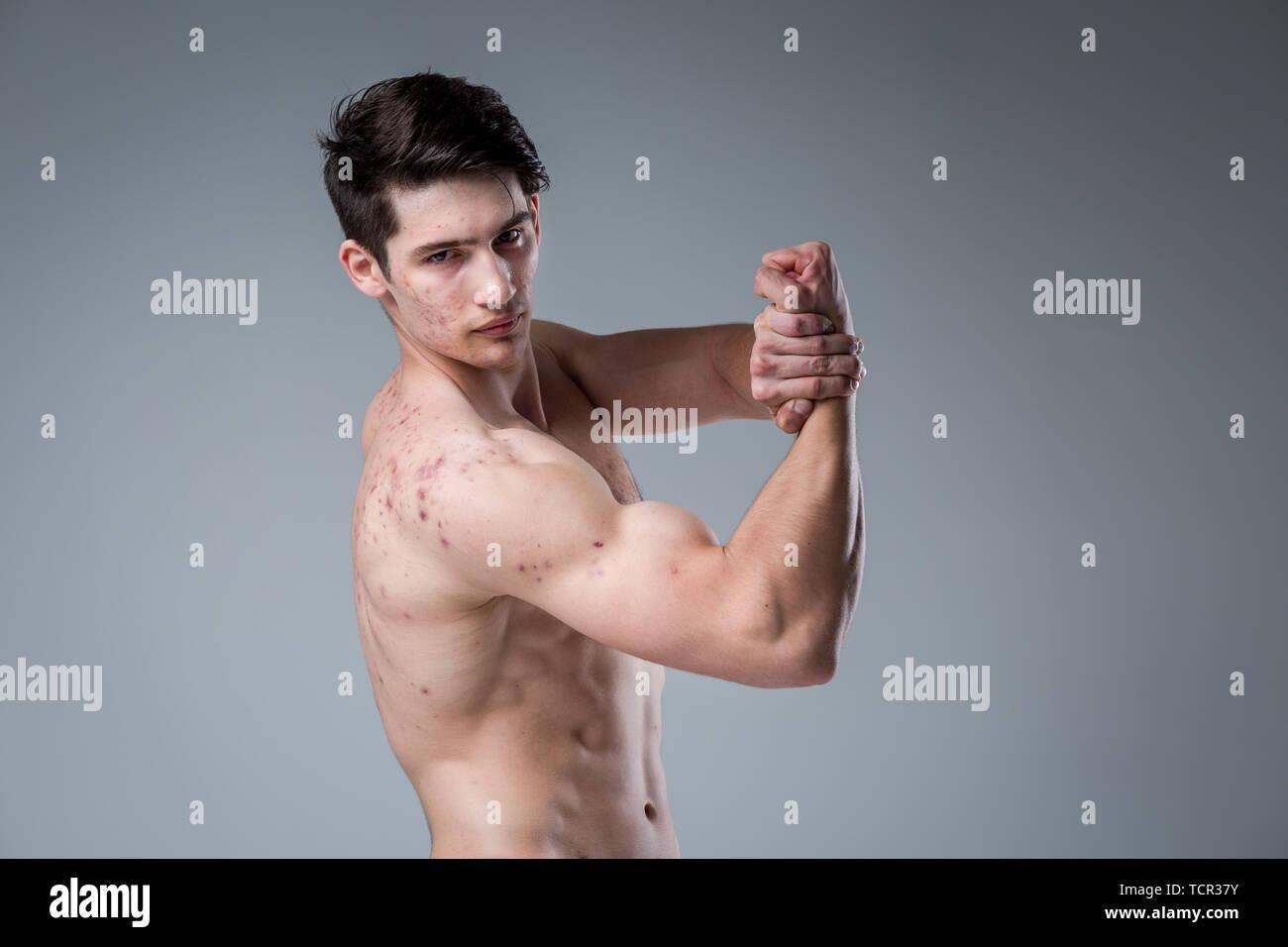 2ddde6fa3422 Ritratto in studio giovane uomo caucasico su sfondo grigio in posa. Tema  della pubertà,