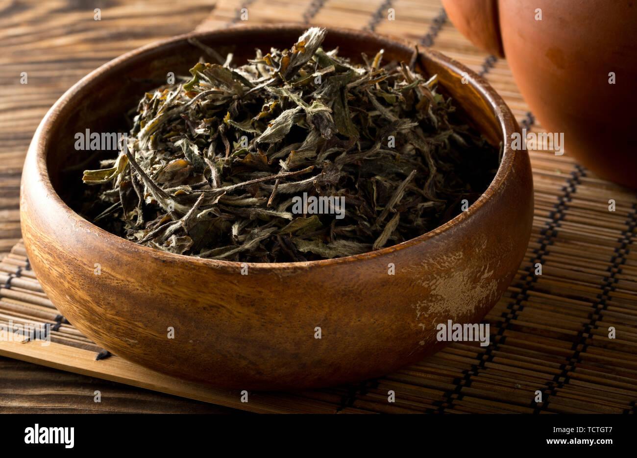 Cumulo di essiccato, crudo Tè bianco lascia nella ciotola di legno sul tappetino di bambù sfondo Foto Stock