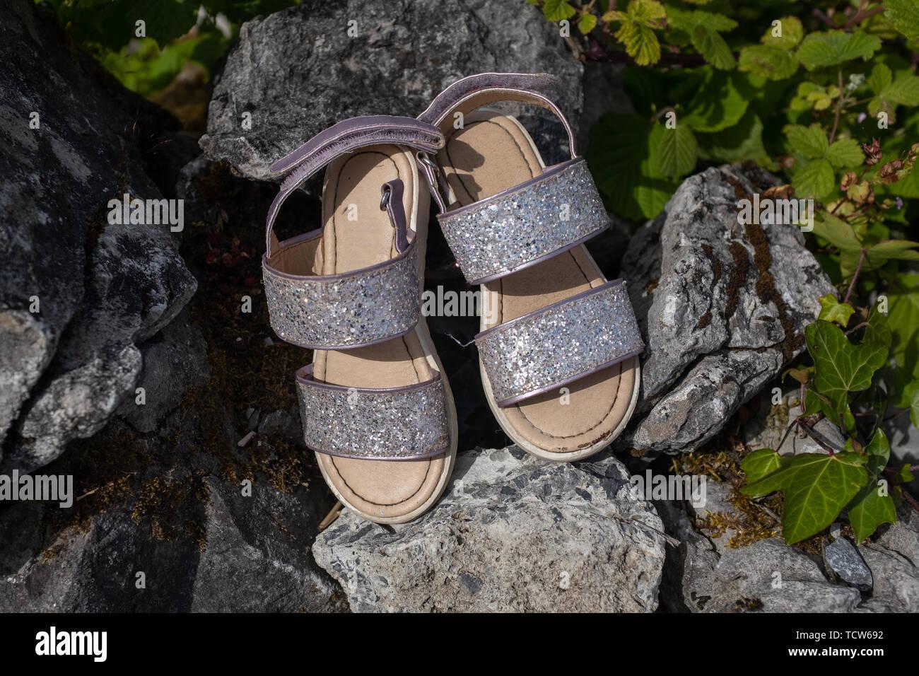 Una coppia di nuovo cercando abbandonato la ragazza vivace sandali lasciati su rocks, nessuno nell'immagine Immagini Stock