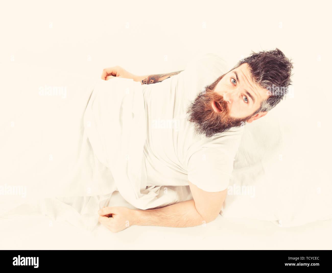 Mattina e wake up concetto. Uomo sulla faccia di sorpresa, mattina, bisogno di alzarsi, sfondo bianco. Uomo con viso assonnato sedersi nel letto, lenzuola bianche, vista dall'alto. Hipster con la barba e baffi risveglio. Immagini Stock