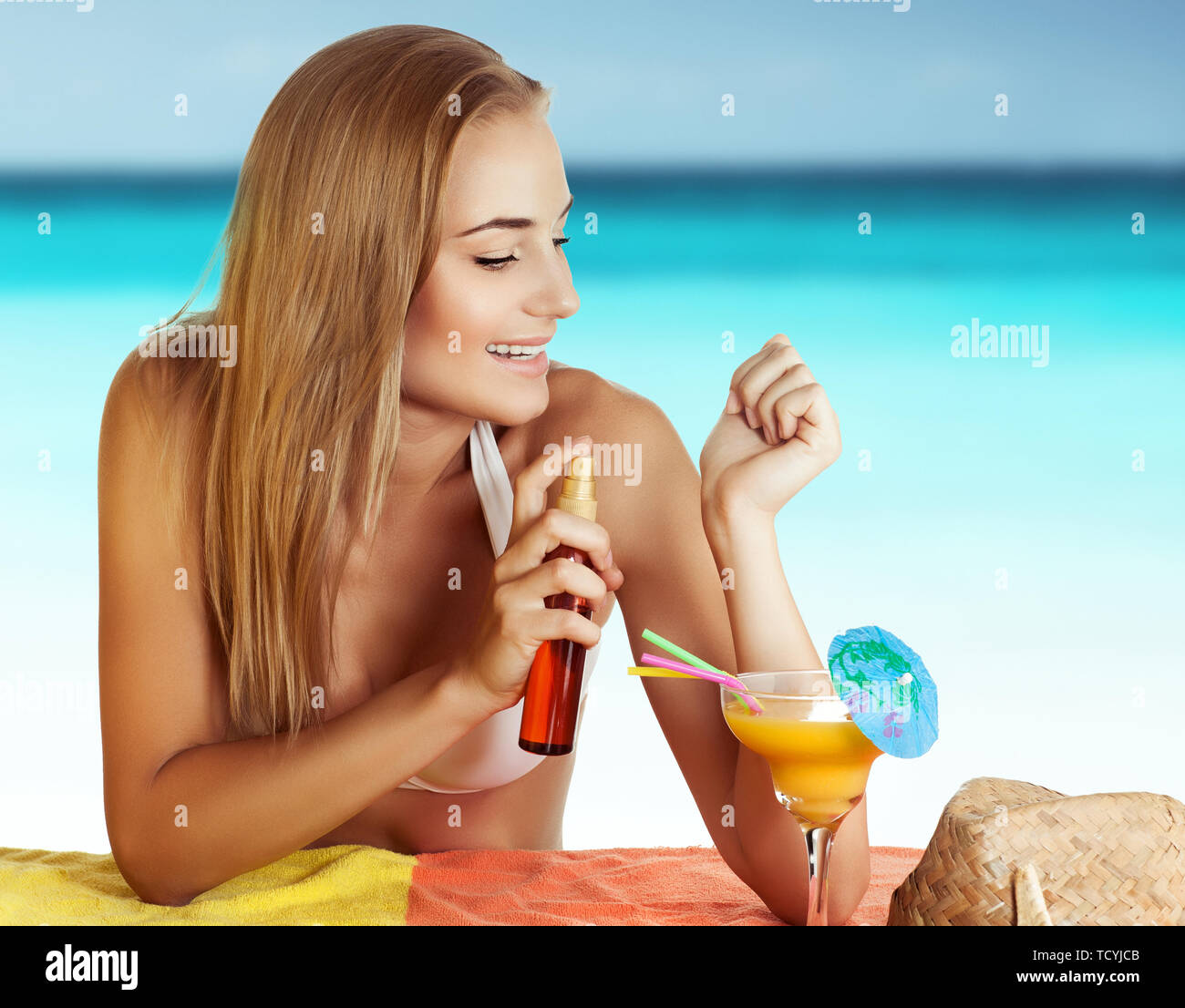 Ritratto di una bella donna felice sulla spiaggia, applicare olio abbronzante, il corpo e la cura della pelle, godendo le vacanze estive Immagini Stock