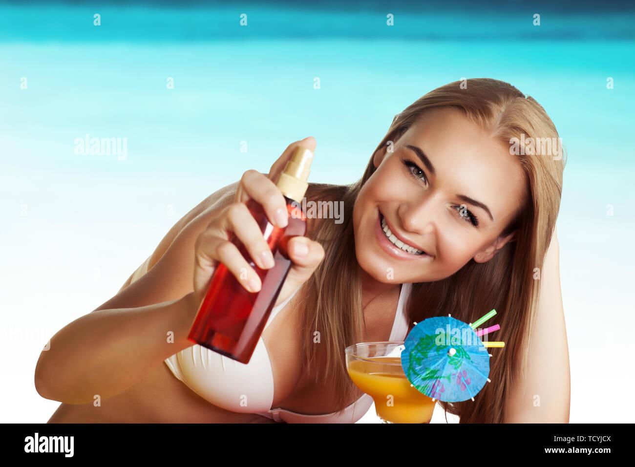 Ritratto di una bella donna trascorrere weekend sulla spiaggia, l'applicazione di crema solare per il corpo, sani e sicuri la concia, bevendo un cocktail sulla spiaggia resort Immagini Stock