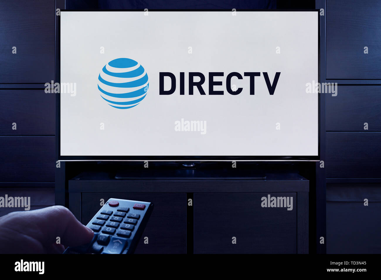 Un uomo punti un telecomando TV al televisore che visualizza il logo per il DirecTV on demand video streaming service (solo uso editoriale). Immagini Stock