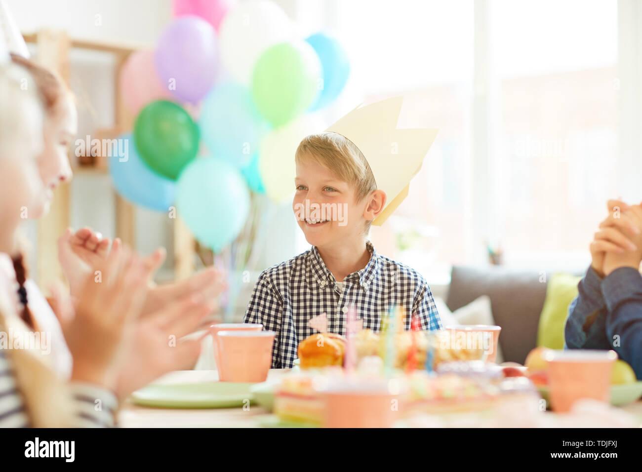 Ritratto di ragazzo sorridente indossando la corona seduta a tavola mentre festeggia il compleanno con gli amici, spazio di copia Foto Stock