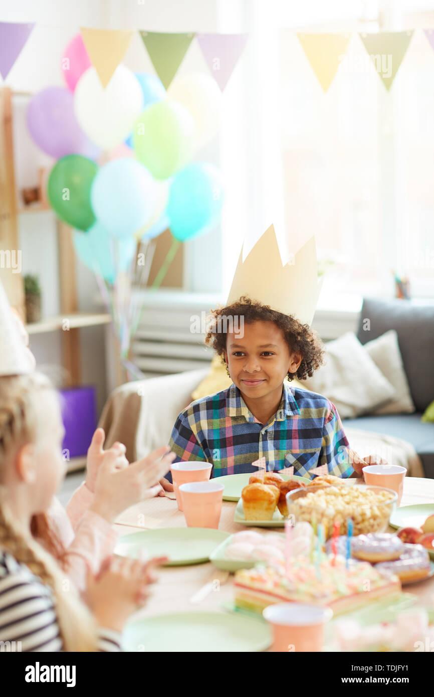 Ritratto di sorridente ragazzo afro-americano che indossa la corona seduta a tavola mentre festeggia il compleanno con gli amici Foto Stock