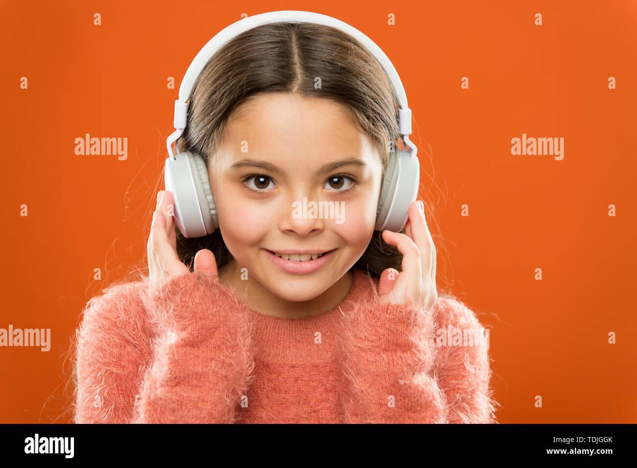 Musica moderna è il suo stile di vita e di piacere. Poco ragazza moderna indossando le cuffie bluetooth. Piccolo bambino ascoltando la musica nella vita di tutti i giorni. Utilizzando le moderne tecnologie nella vita quotidiana. La vita moderna. Immagini Stock