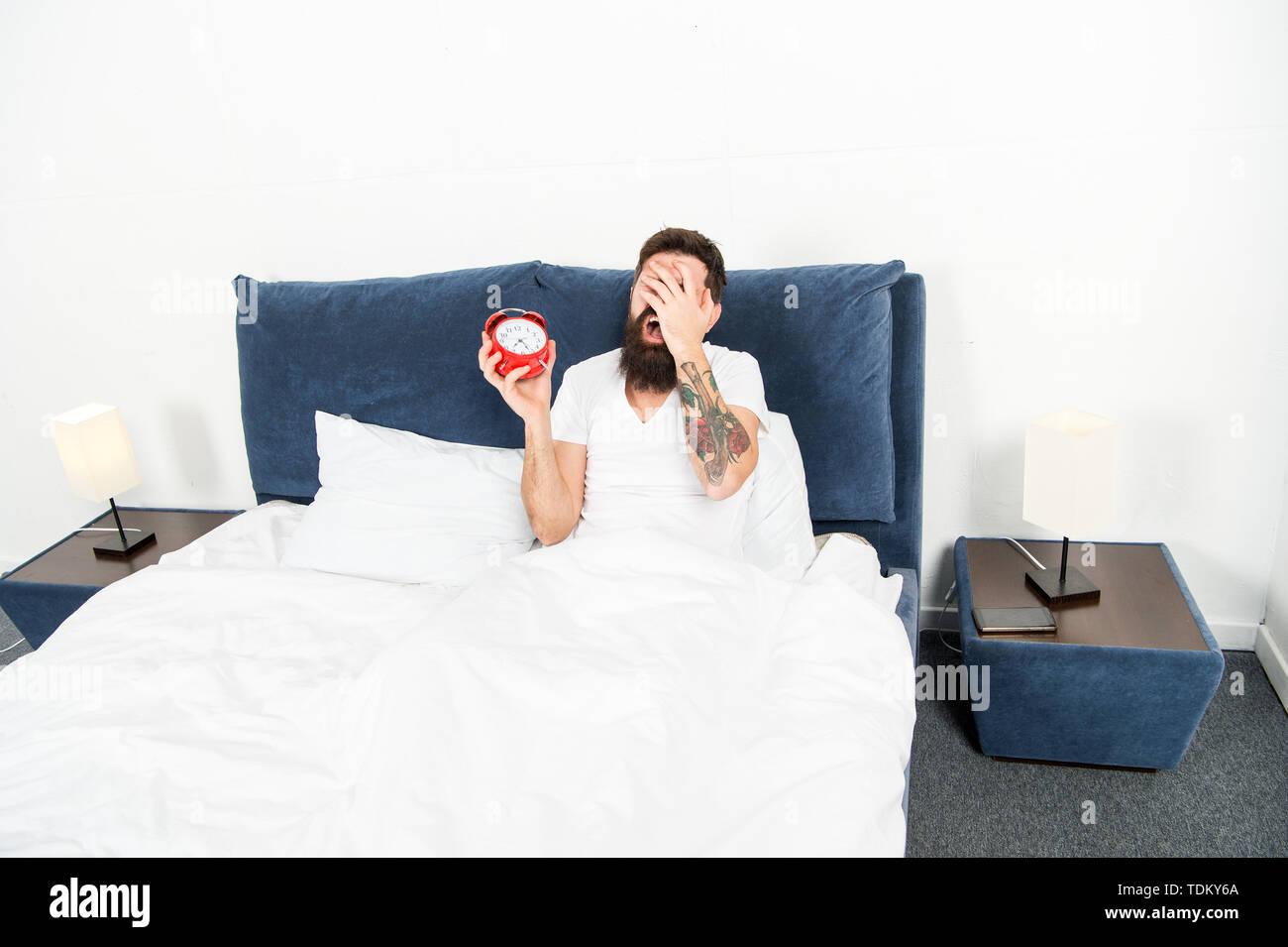 Uomo Barbuto hipster odio svegliarsi presto. L'energia distruttiva. Più difficile momento della giornata. È del tutto normale per odiare il vostro suono di allarme. Odioso pianificazione. Migliori orologi di allarme per le persone che odiano la mattina. Immagini Stock