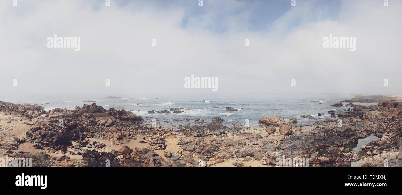Spiaggia rocciosa con un nuvoloso vista sull oceano Atlantico in Portogallo Immagini Stock