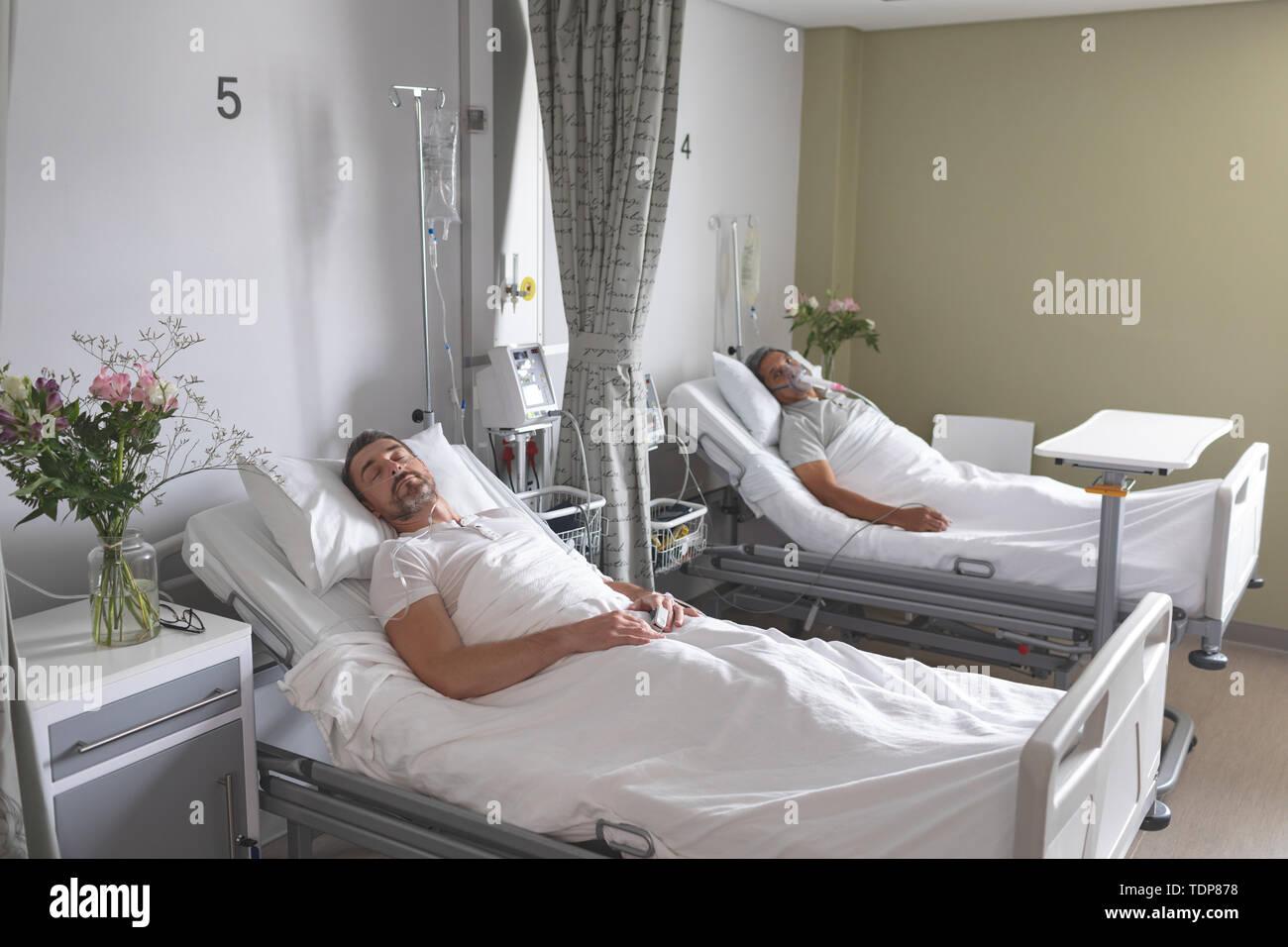 I pazienti di sesso maschile dormire nel letto per il reparto Foto Stock