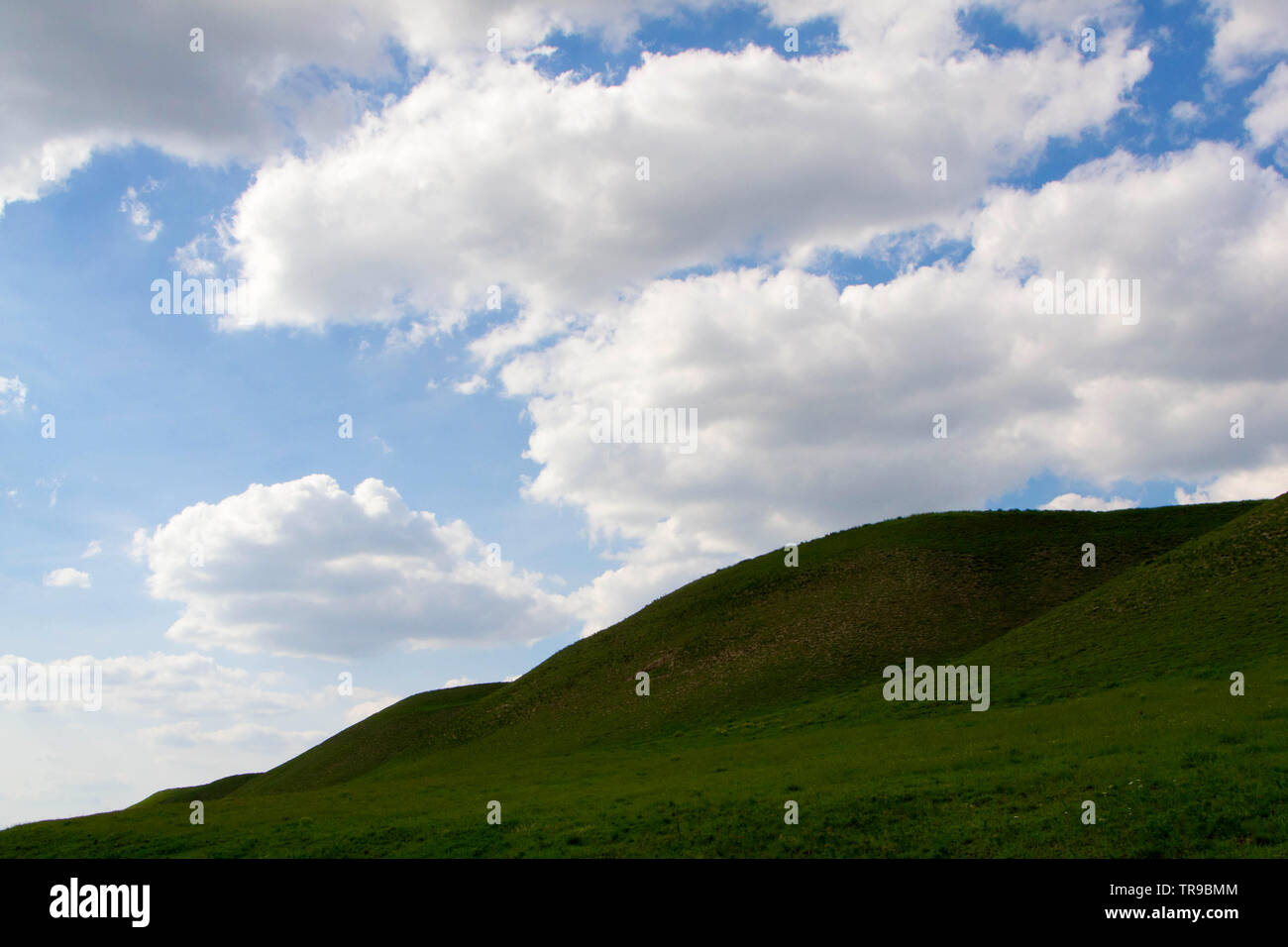 Una collina con puffy clouds overhead. Titel hill, Serbia. - Immagine Immagini Stock