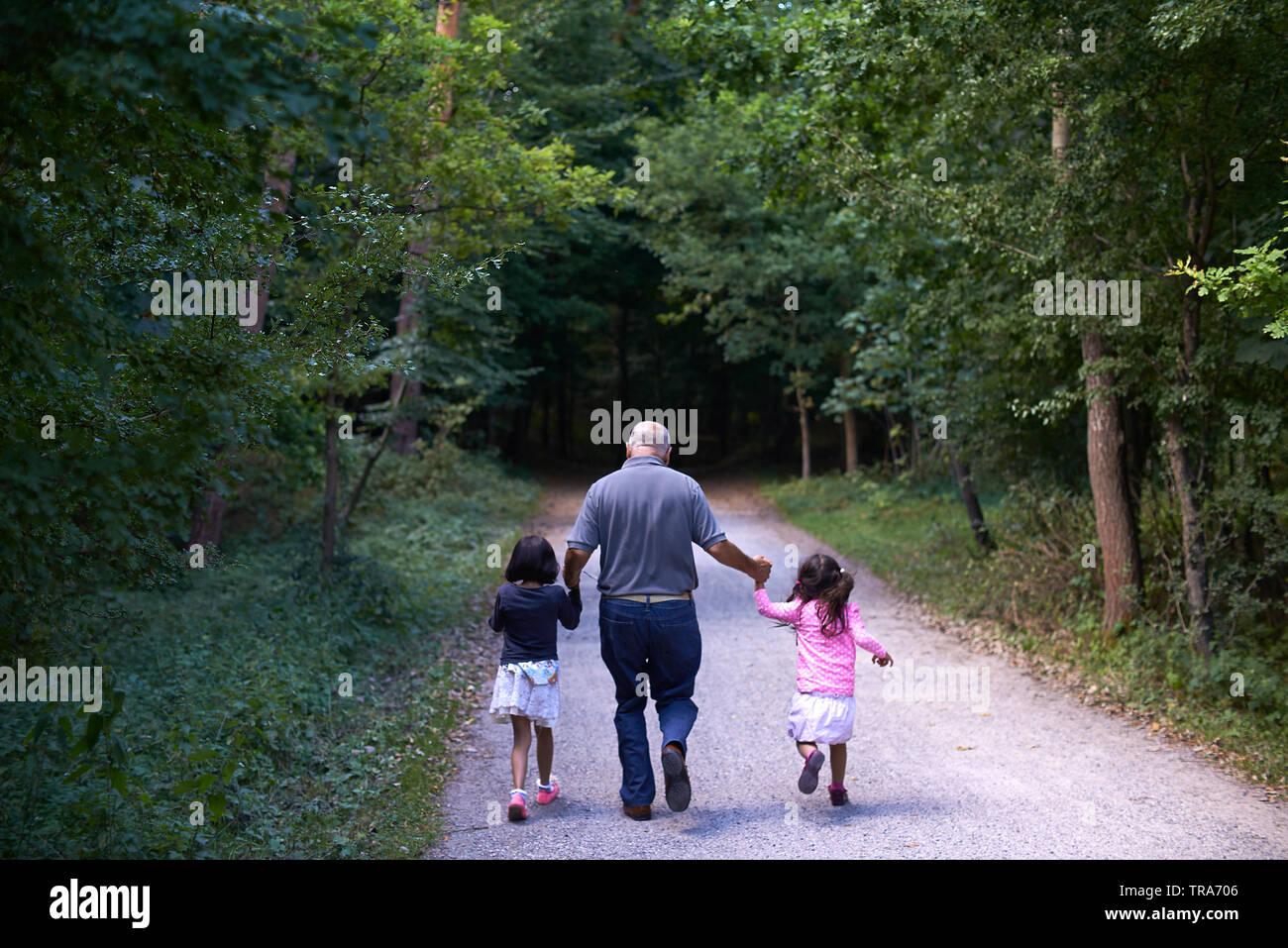 Nonno caucasica camminando mano nella mano con i suoi due giovani grand i bambini nel parco Immagini Stock