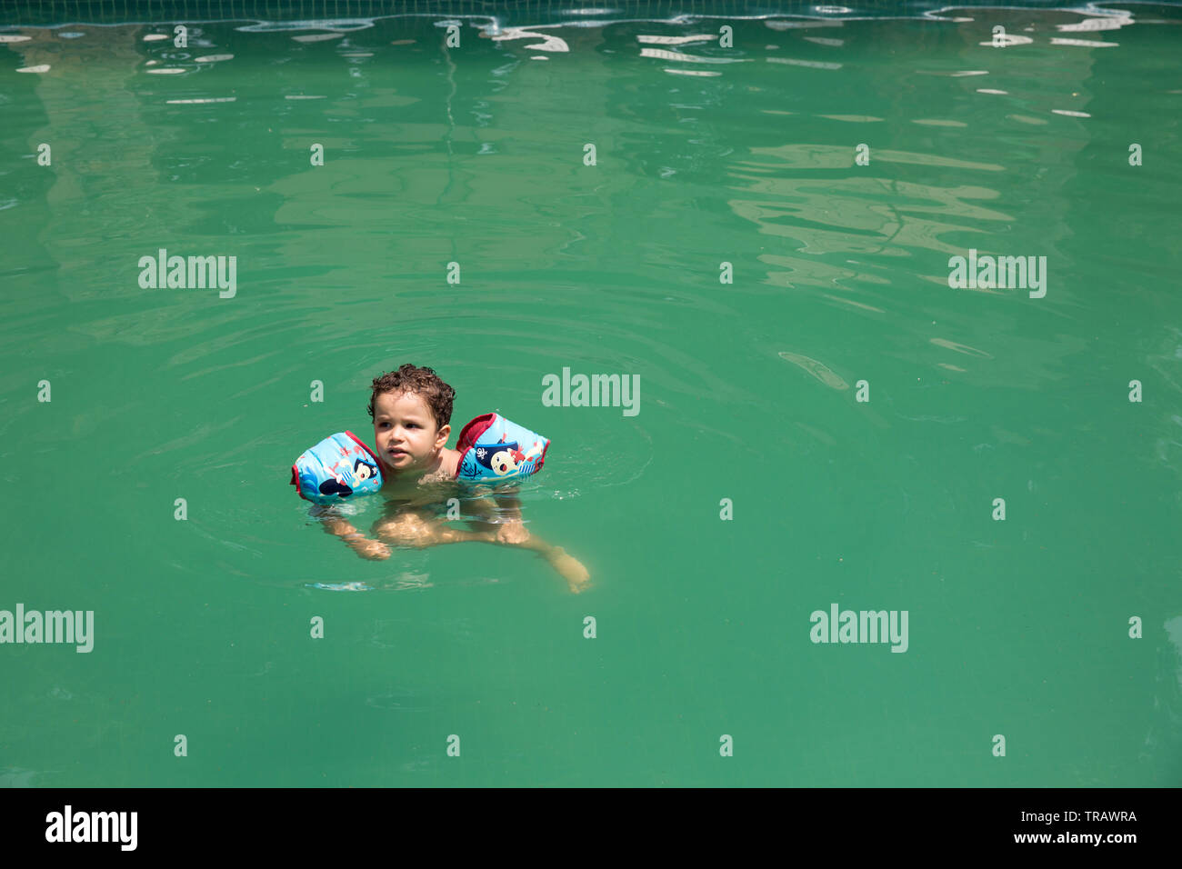 Un due-anno-vecchio figlio di nuoto in una piscina sporca con acqua verde in Messico. Fotografia di Bénédicte Desrus Immagini Stock