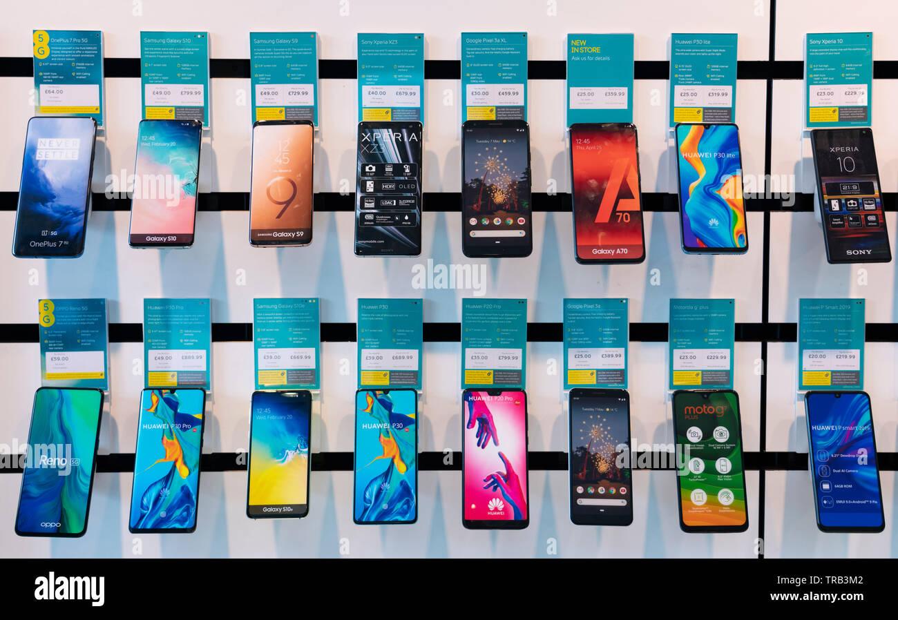 Righe di nuovi telefoni intelligenti sul display in EE mobile phone shop Immagini Stock