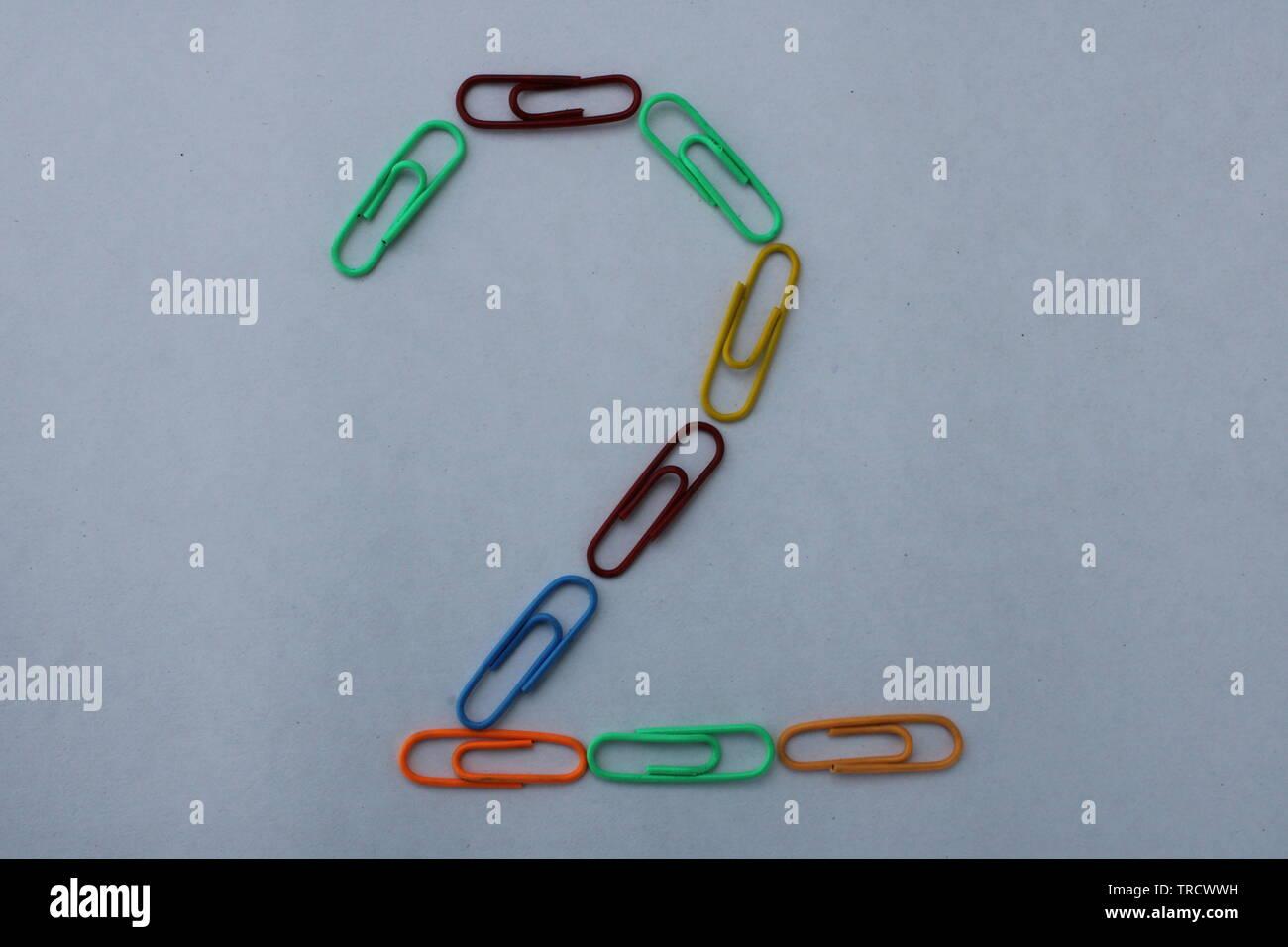 Numero 2 realizzato con carta colorata clip su sfondo bianco Foto Stock