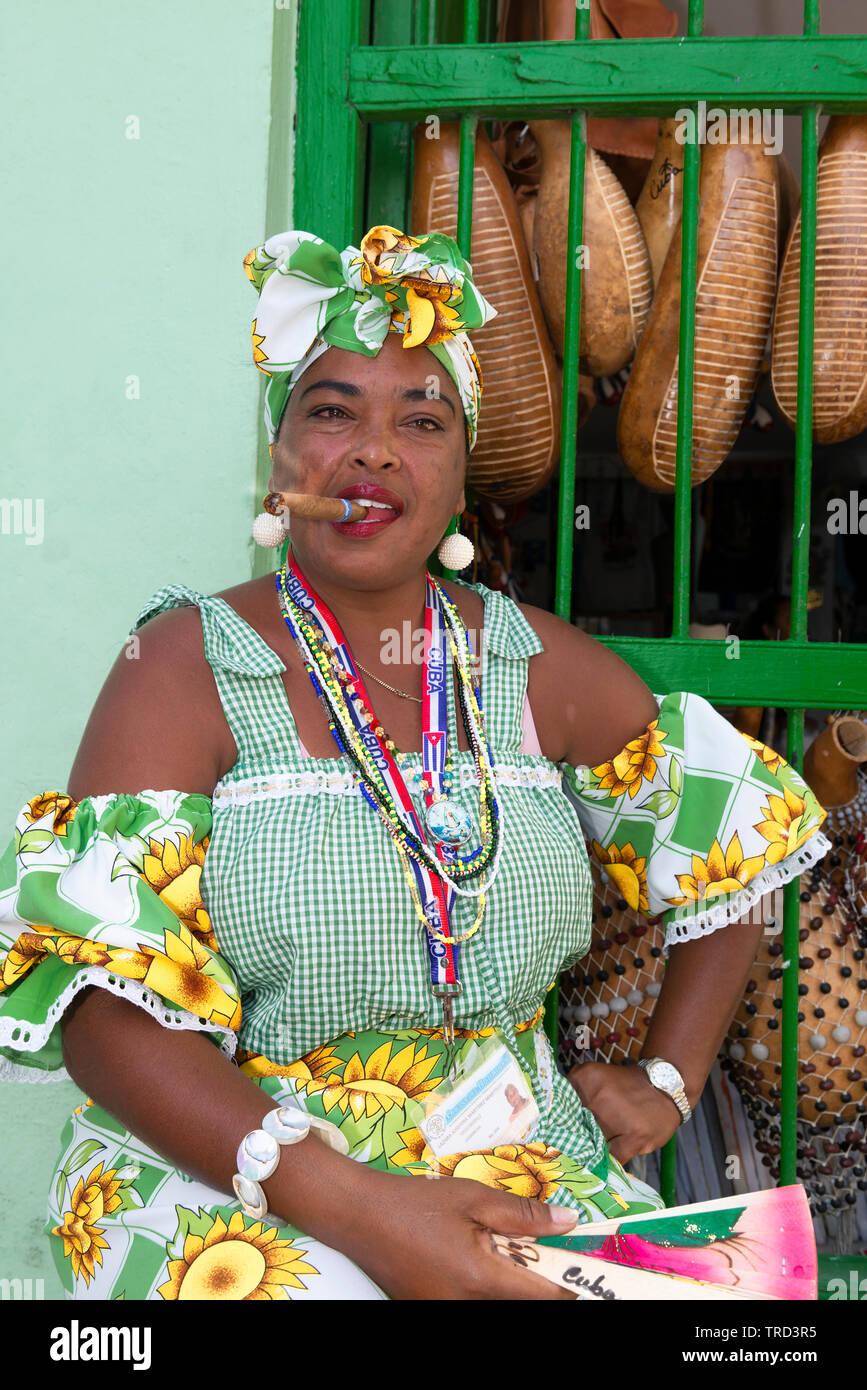 Colorfully vestito donna cubana seduta di fumare un sigaro di grandi dimensioni in una delle strade della città vecchia di l'Avana, Cuba, Caraibi Foto Stock
