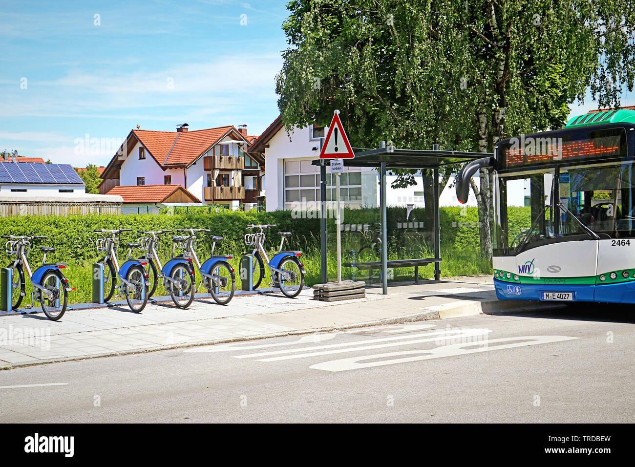 A Garching, Germania - Biciclette elettriche pronto a noleggiare convenientemente allineati sul marciapiede vicino alla fermata del bus. Foto Stock