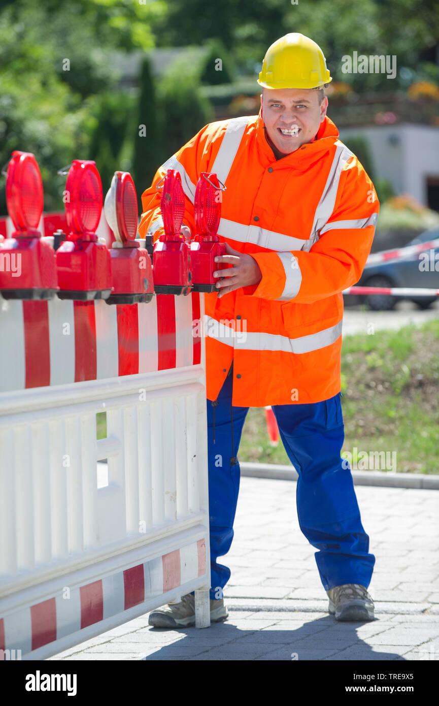In Bauarbeiter orangener Signalweste, eine Strassenabsperrung aufbauend | operaio edile in un arancio ad alta visibilità giacca, installando un roadblo Immagini Stock