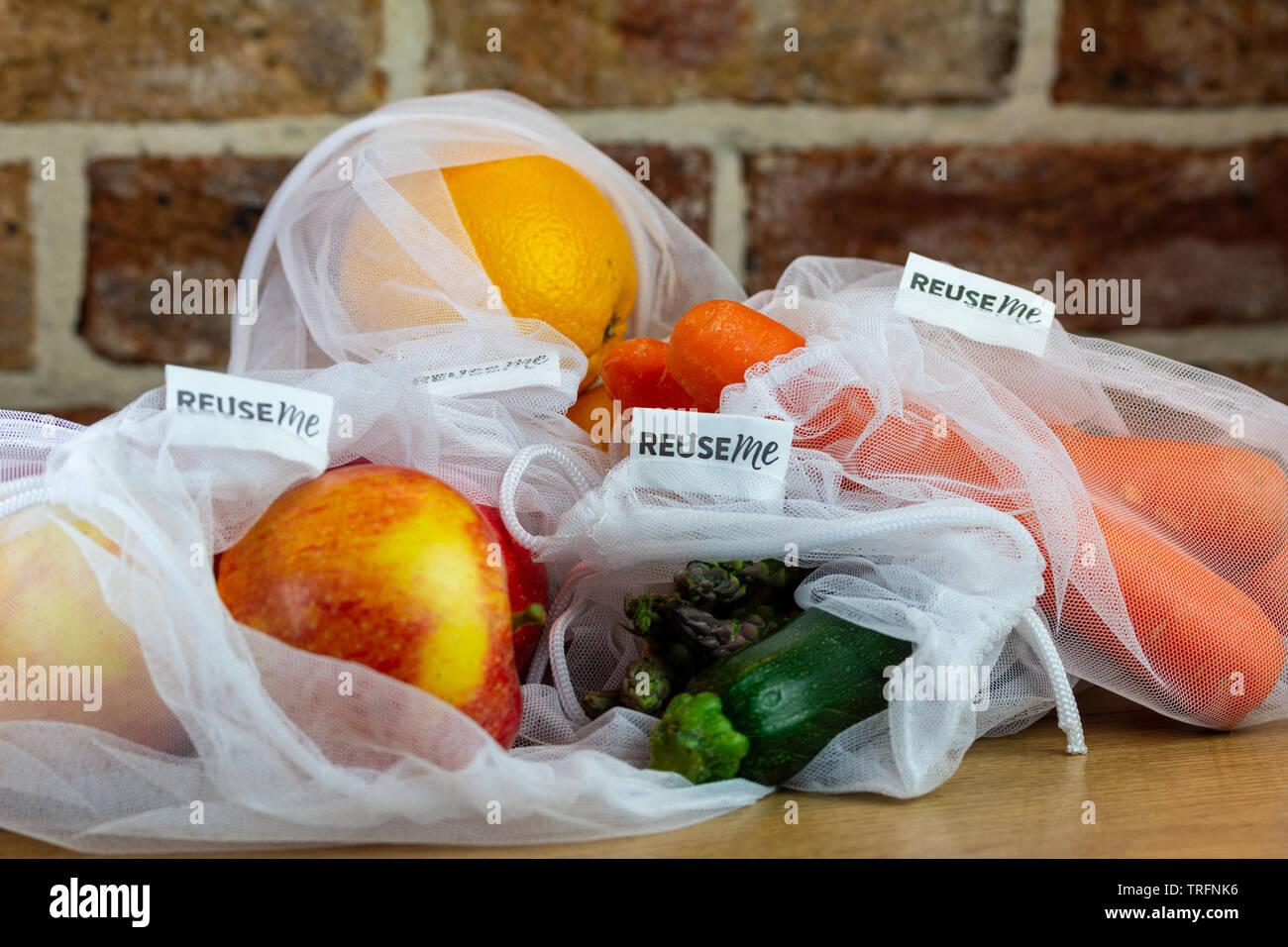 La frutta e la verdura riutilizzabili in borse di maglia, con il riutilizzo di me etichette, sul banco di cucina, autentica reale libero di plastica eco friendly shopping Immagini Stock