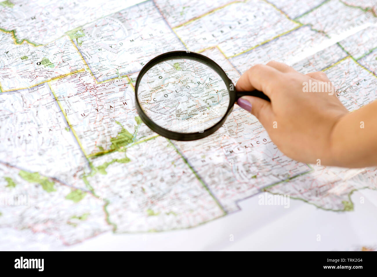 Una femmina utilizza una mappa e di una lente di ingrandimento per pianificare il suo viaggio Immagini Stock