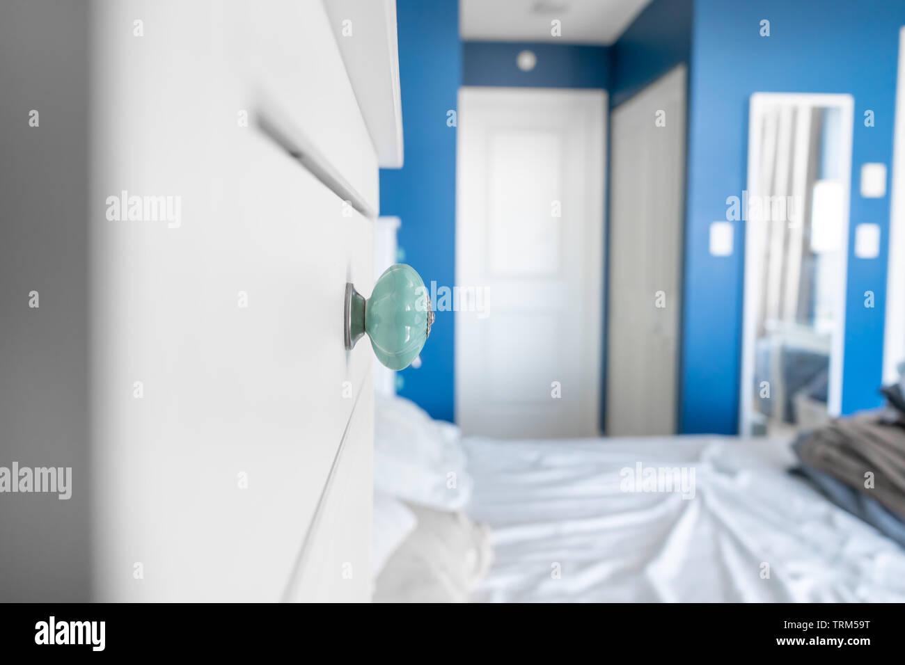 Vista prospettica di una camera da letto che mostra un comò la manopola blu, pareti dipinte di bianco, accenti e un letto senza coperte, con disordine, stropicciato le lenzuola. Immagini Stock