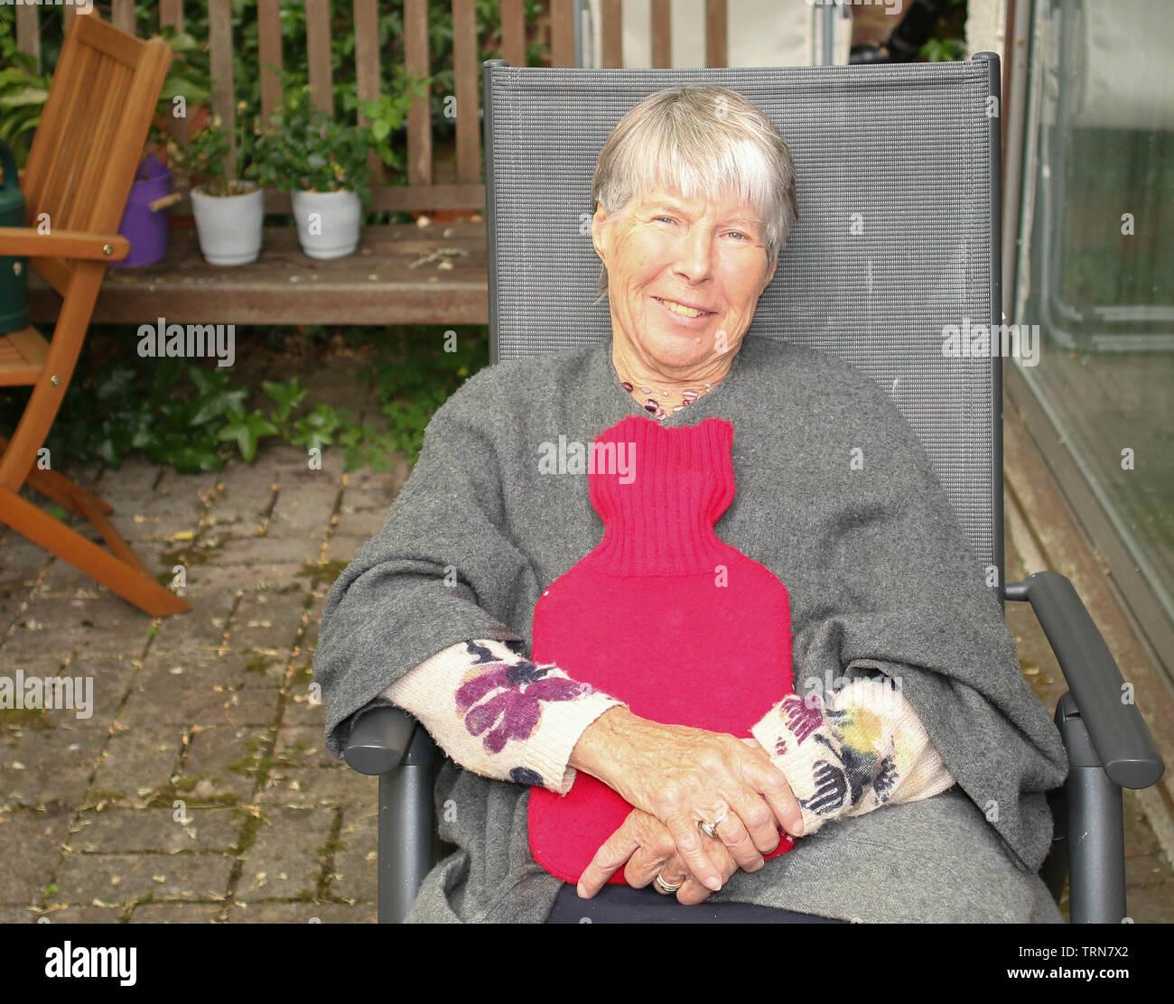 OAP, donna seduta al sole con bottiglie di acqua calda. Immagini Stock