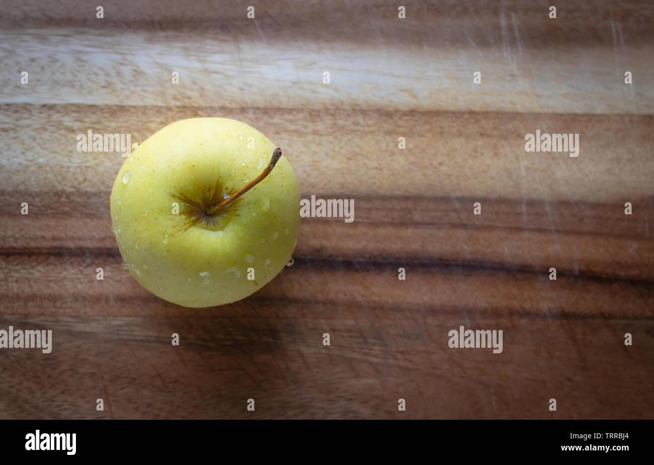 Una mela Golden Delicious su un tagliere di legno in formato orizzontale. Foto Stock