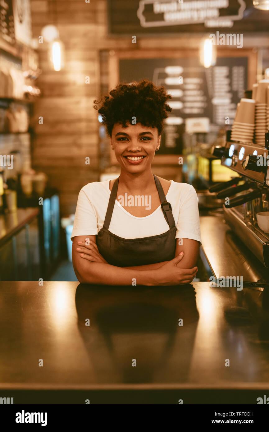 Sorridente donna africana nel grembiule permanente al cafe contatore. Fiducioso barista femmina in piedi dietro il contatore. Foto Stock