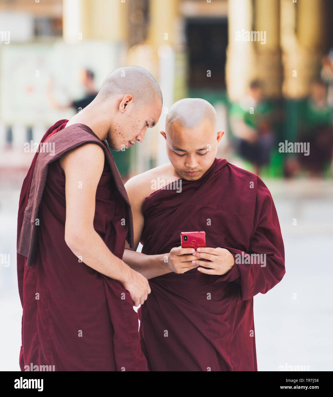 Yangon, Myanmar - Marzo 2019: giovane buddista novizio monaci con i gadget in Shwedagon pagoda tempio complesso. Cerca sulla schermata telefono. Foto Stock