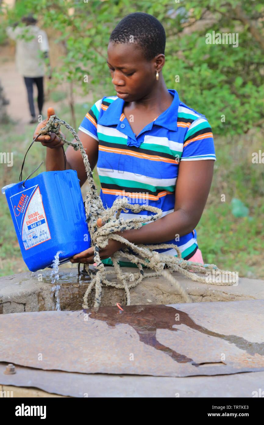 Adolescente togolaise tirant de l'eau d'onu puits. Datcha Attikpayé. Il Togo. Afrique de l'Ouest. Immagini Stock