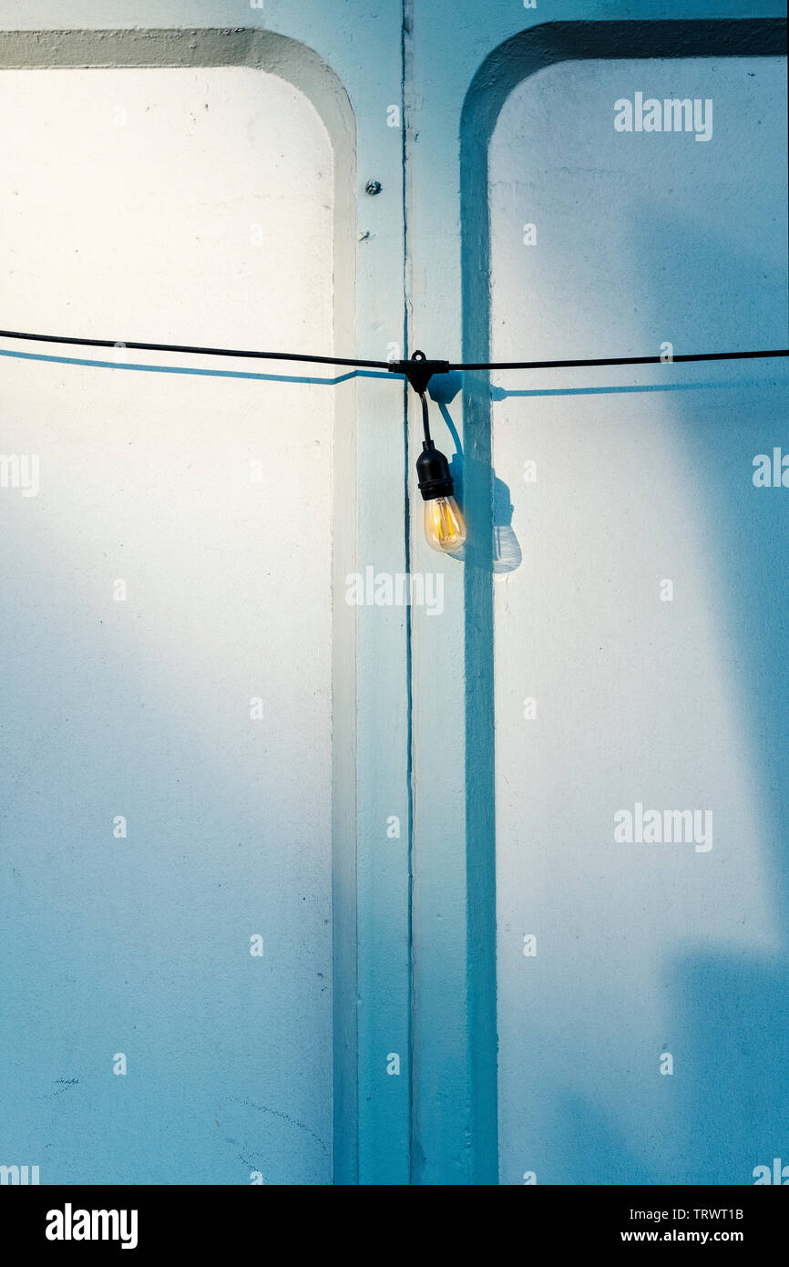 Spia di bassa tensione sulla lampadina blu pallido muro -abstarct concept Foto Stock