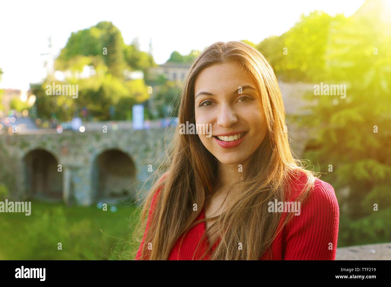 Ritratto di sorridente giovane donna con la luce solare e flare spazio di copia Foto Stock