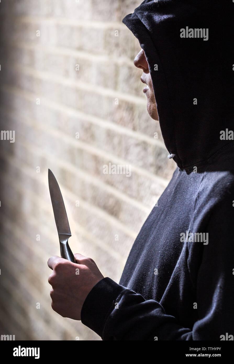 Taglierini, adolescente in una felpa con cappuccio che porta un coltello su strada nel Regno Unito Immagini Stock