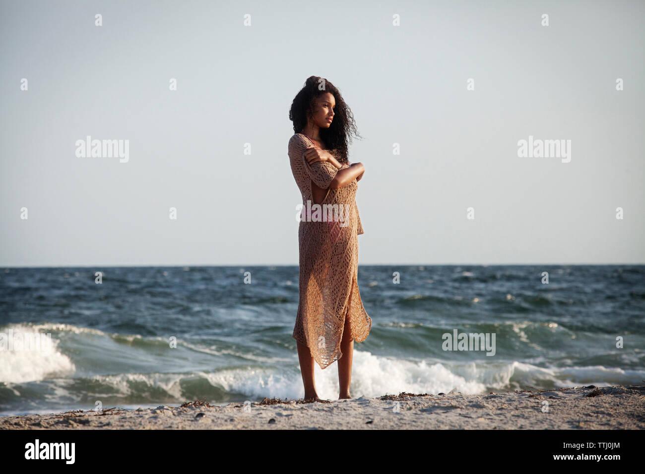 Ragazza adolescente in sarong permanente sulla riva presso la spiaggia Immagini Stock