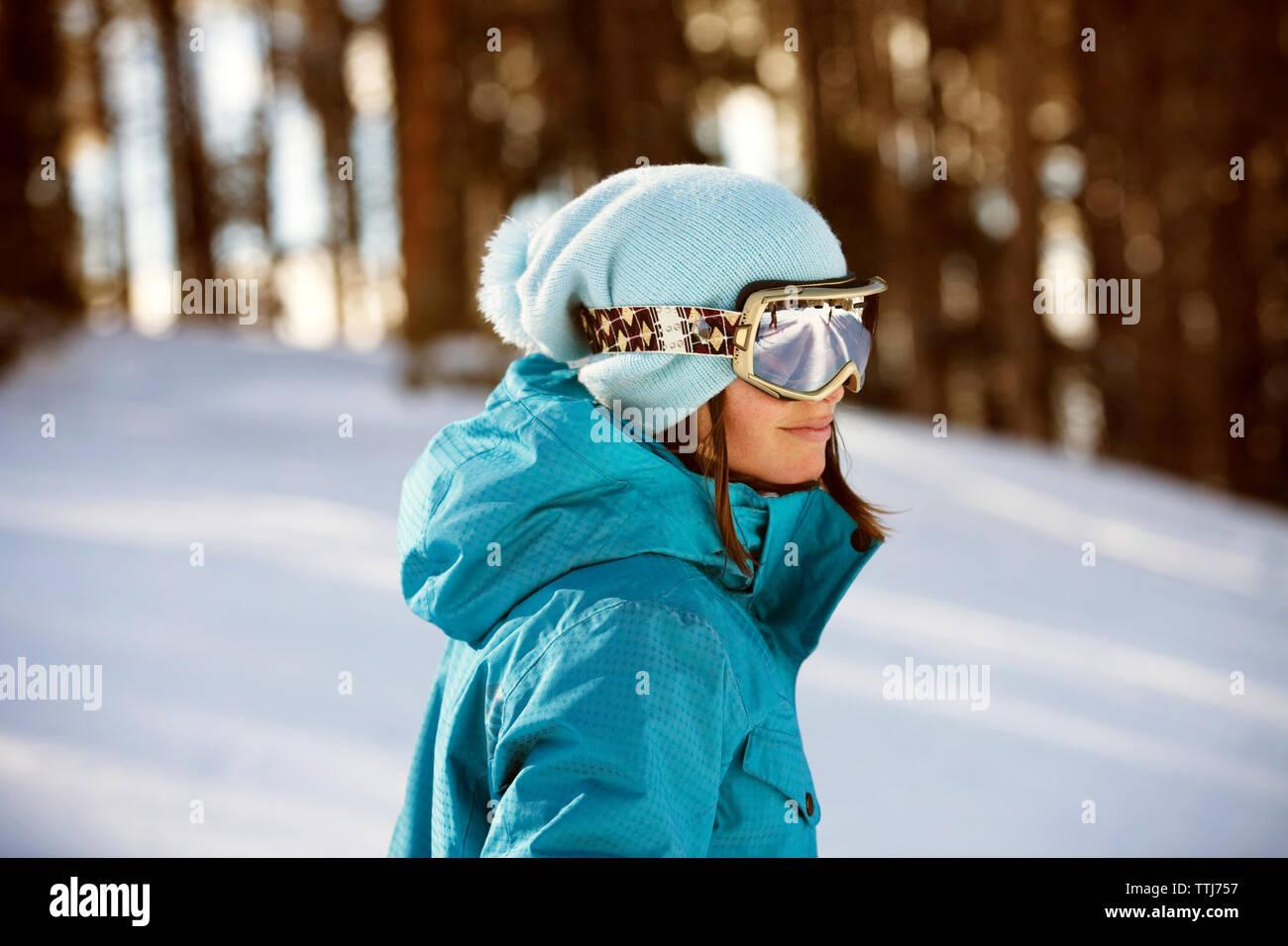 Donna che indossa gli occhiali da sci in piedi sul campo nevoso Immagini Stock